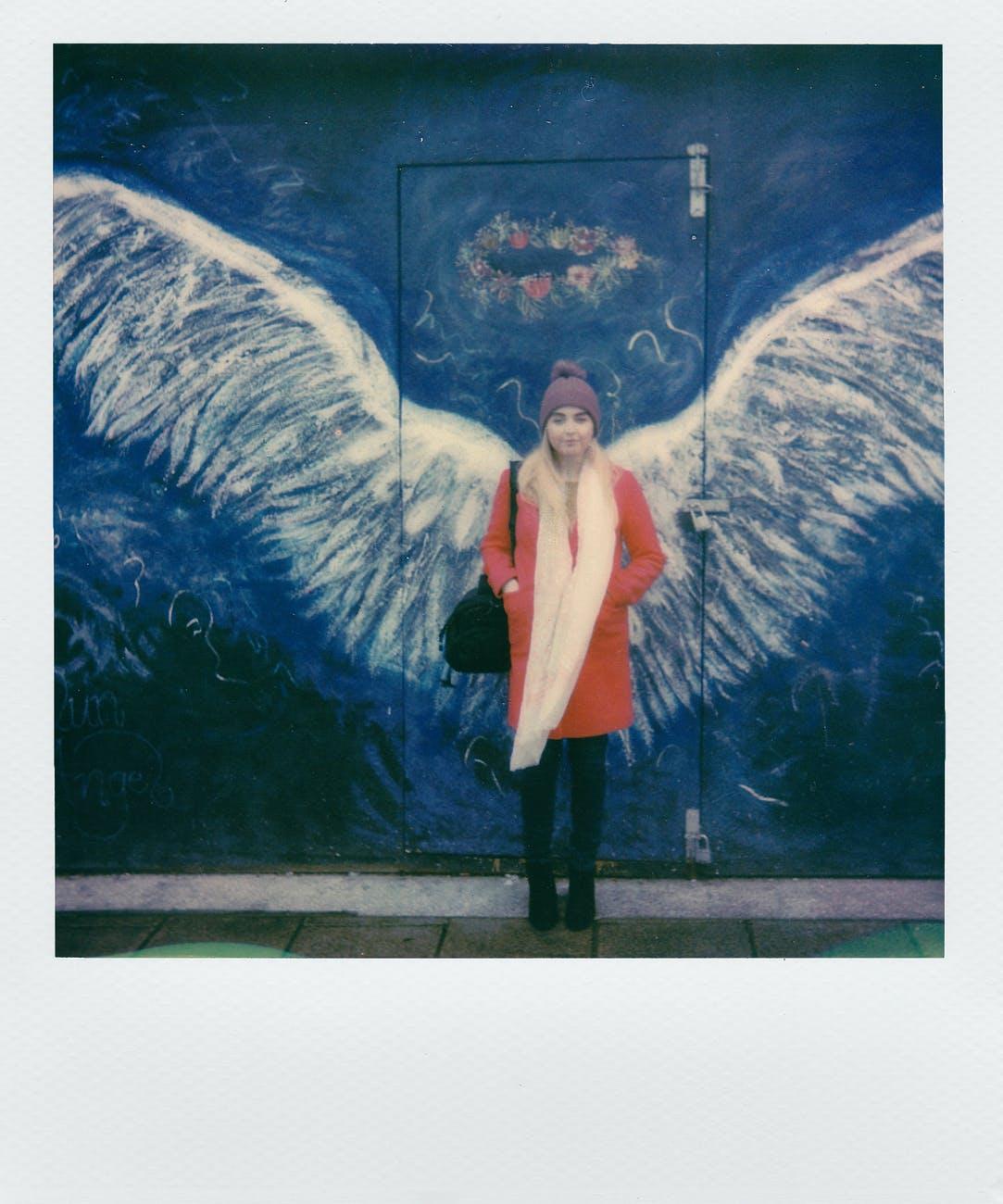 woman in orange coat standing in front of angel wings