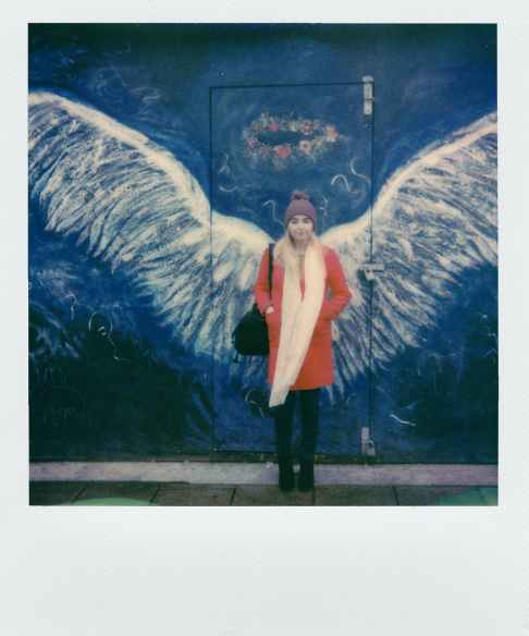 woman in orange coat standing in front of angel wings